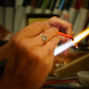 Hände halten eine Glasstab und schmelzen ihn an der Flamme