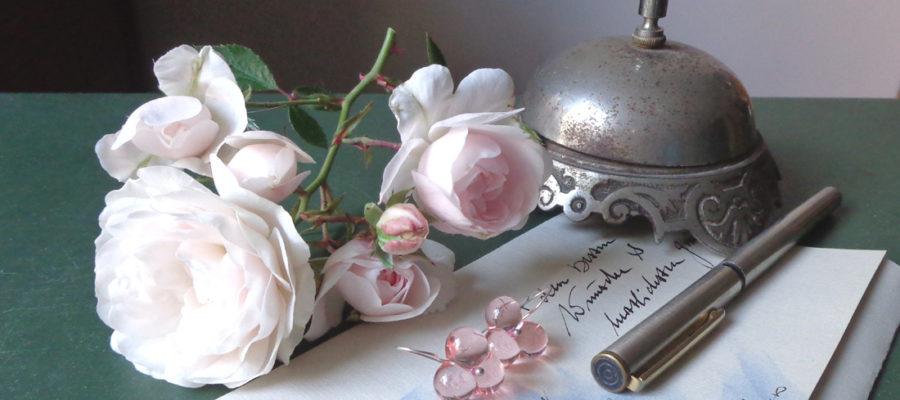 Brief mit Rosen, zwei Ohrringe aus rosa Glas, Füller, silberne antike klingel