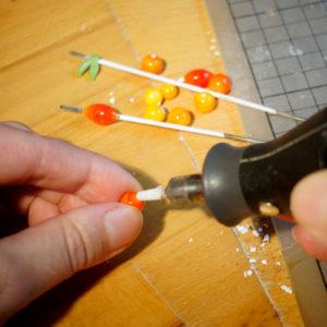 Glasperlen mit Dremel geschliffen, Glasperlen auf Metallstab, Hände