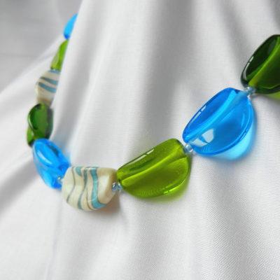 Halskette aus 20 handgefertigten Glasperlen. Unikat von schmuckes Glas. Transparentes grünes und türkisenes Glas. Perlen aus Glas in elfenbein. 52 cm lang.