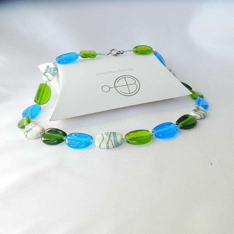 Halskette aus 20 handgefertigten Glasperlen. Unikat von schmuckes Glas. Transparentes grünes und türkisenes Glas. Perlen aus Glas in elfenbein. 52 cm lang. Schachtel mit Logo von schmuckes Glas.