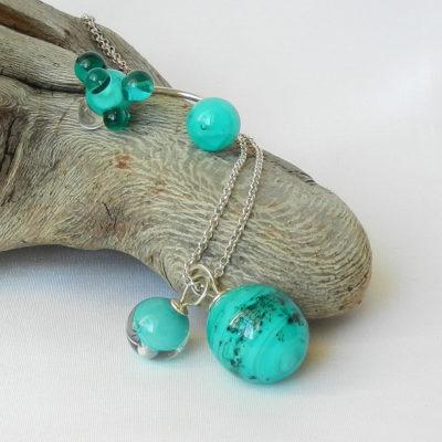 Silberring mit zwei handgefertigten Glasperlen in leuchtendem seegrün, eine silberkette mit einer großen und einer kleinen Glaskugel als Anhänger an einer Silberkettenikat