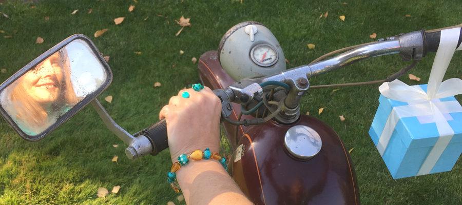 Künstlerin mit braunem Glasperlenarmband auf Moped, Geschenkschachtel, Spiegel, SR2